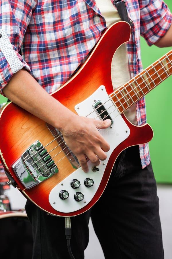 Midsection профессиональной играя гитары в студии звукозаписи стоковое изображение rf
