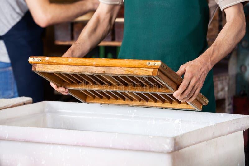 Midsection работника окуная прессформу в пульповидной воде стоковые фотографии rf