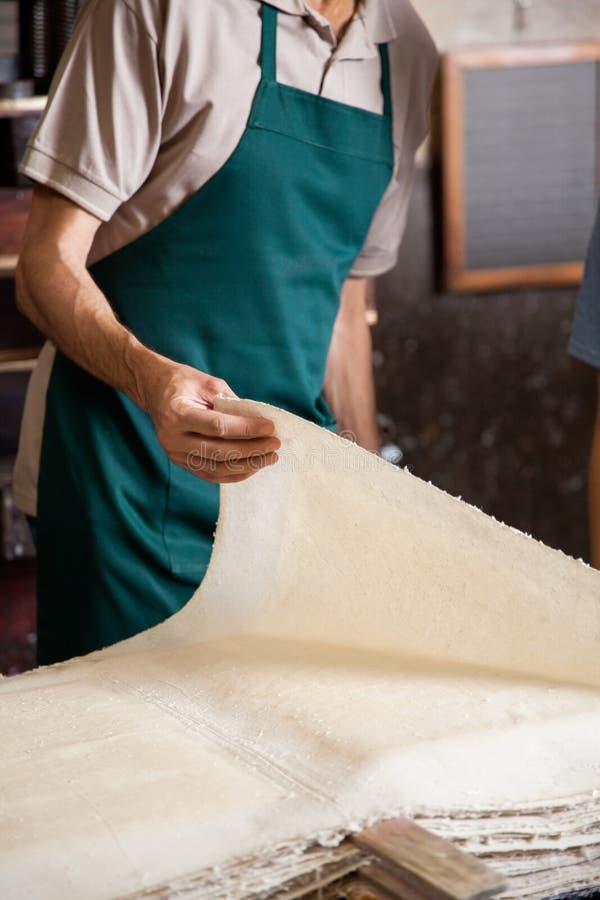 Midsection работника проверяя бумажные листы на стоковое изображение rf