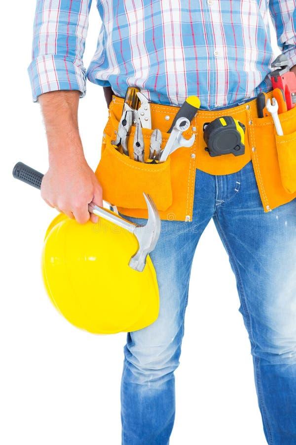 Midsection работника физического труда держа защитный шлем и молоток стоковое фото