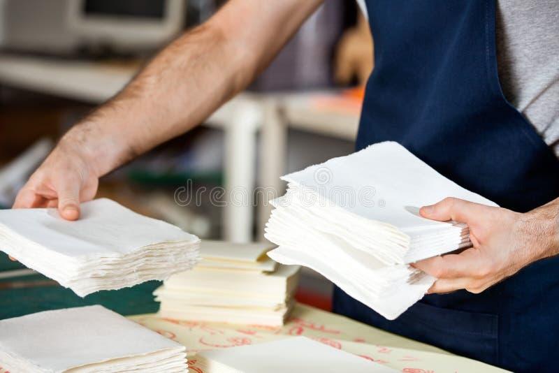 Midsection работника штабелируя бумаги в фабрике стоковая фотография rf