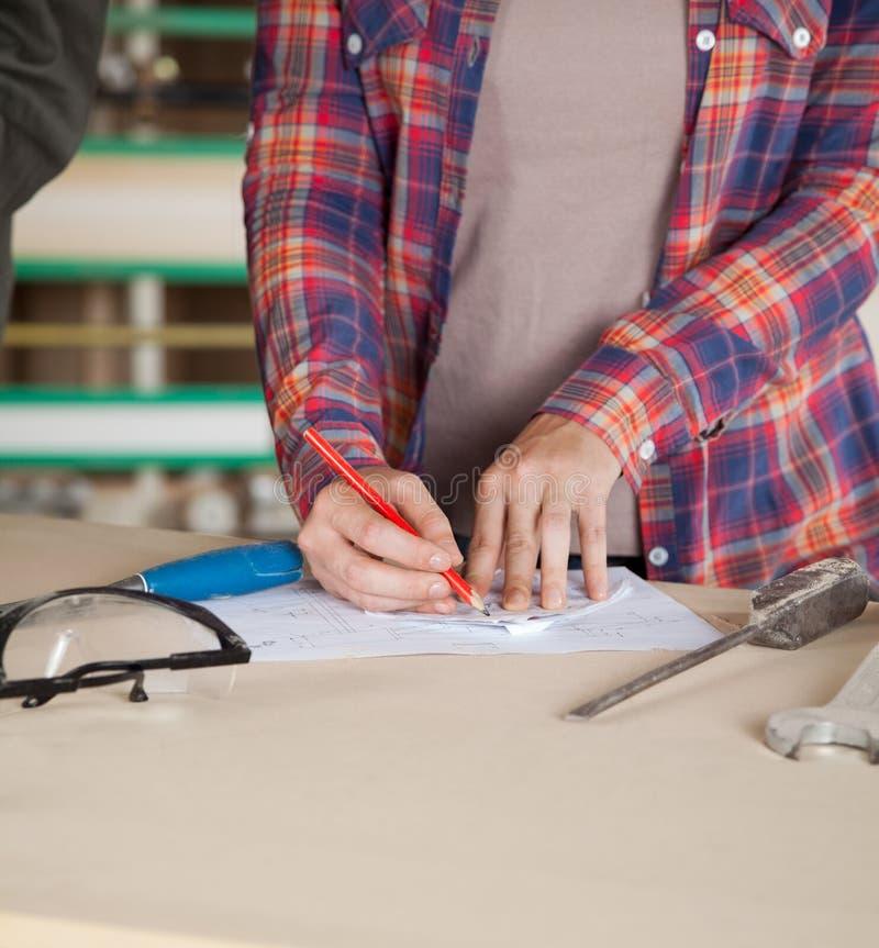 Midsection светокопии чертежа работника стоковая фотография