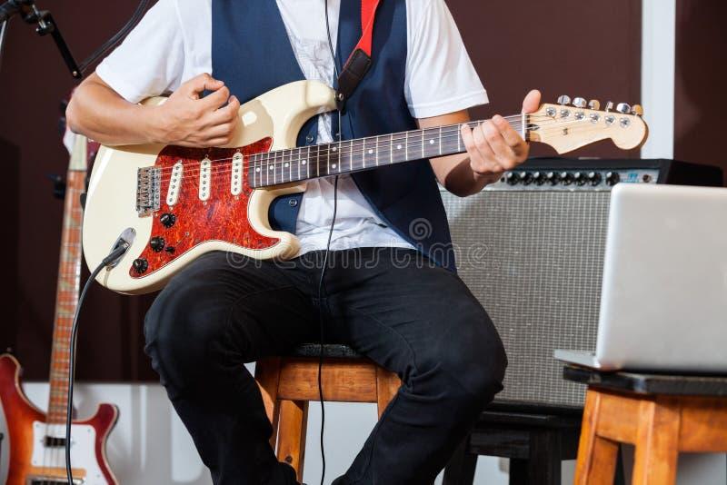 Midsection совершителя играя электрическую гитару стоковые фотографии rf