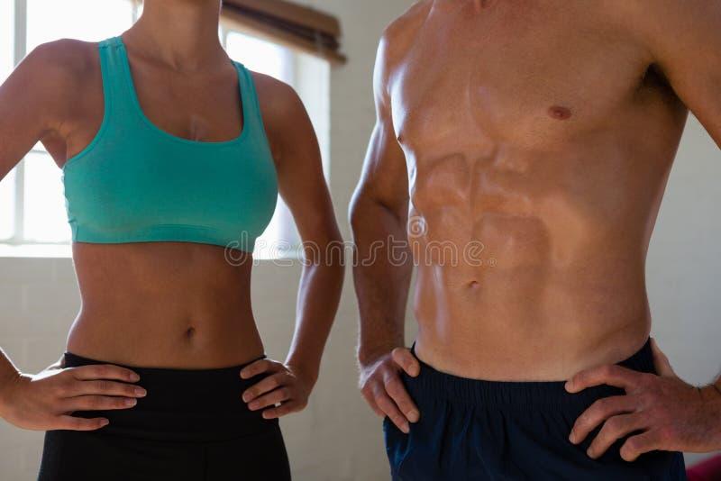 Midsection спортсменов пригонки с руками на бедре на студии фитнеса стоковое изображение
