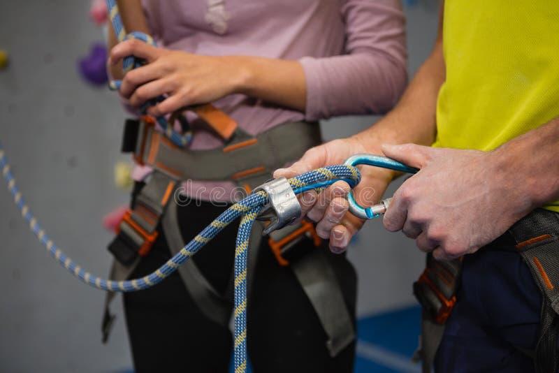 Midsection спортсменов регулируя ремни безопасности в клубе стоковые фото