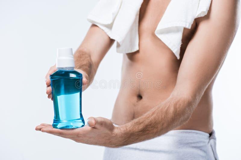 Midsection человека с полотенцем ванны на плече и вокруг талии держа бутылку rinse зуба в руках, стоковые фотографии rf