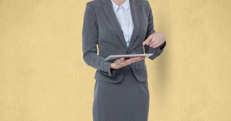 Midsection av affärskvinnan som använder den digitala minnestavlan mot gul bakgrund stock illustrationer