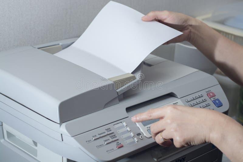 Midsection av affärskvinnan som använder faxmaskinen fotografering för bildbyråer
