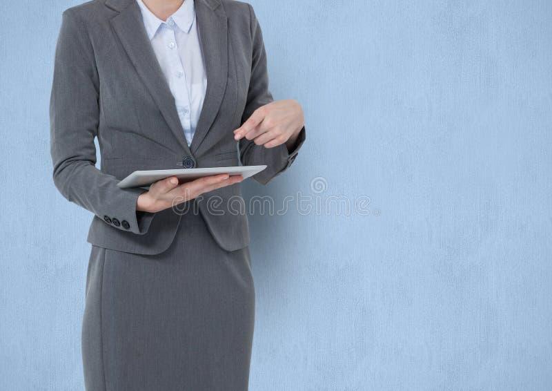 Midsection av affärskvinnan som pekar på minnestavlaPC:N över blå bakgrund royaltyfri foto