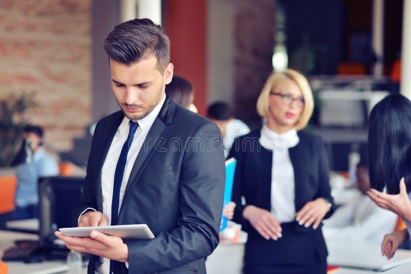 Midsection av affärsmannen som i regeringsställning använder den digitala minnestavlan royaltyfri foto