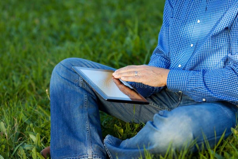 Midsection av affärsmannen Using Digital Tablet på gräs royaltyfri fotografi