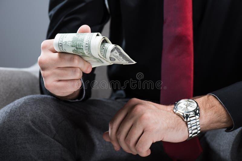 Midsection av affärsmansammanträde i fåtölj- och innehavpengar i hand, arkivfoto