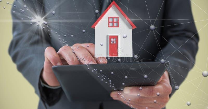 Midsection av affärspersonen som rymmer den digitala minnestavlan med huset och förbinder prickar stock illustrationer