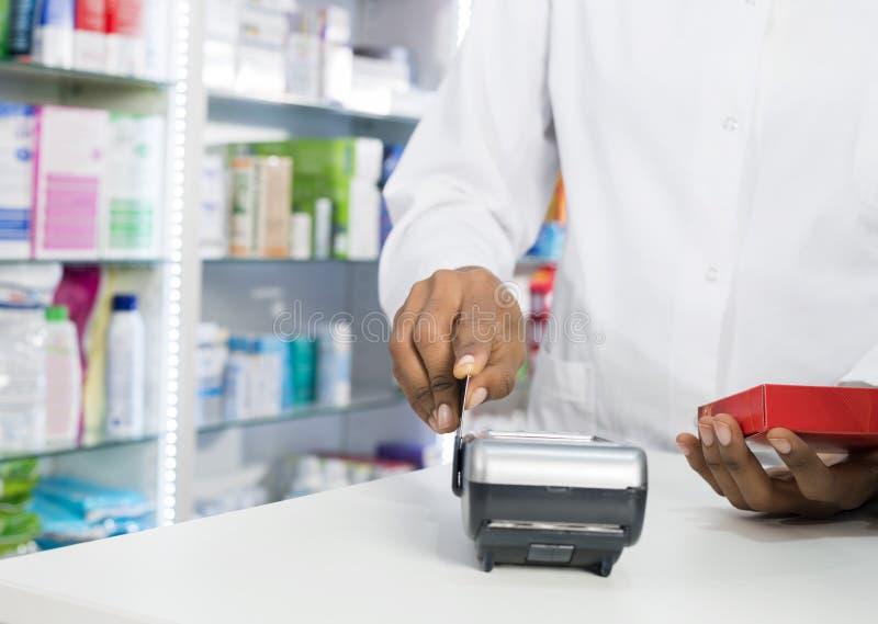 Midsection av apotekaren Swiping Credit Card, medan rymma Produ arkivbilder