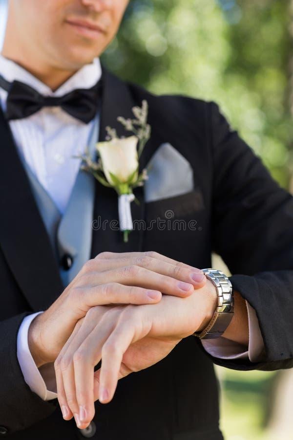 Midsection av brudgummen som kontrollerar tid royaltyfria bilder