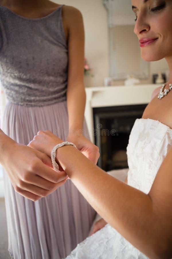 Midsection av brudtärnan som hjälper bruden, i att få klätt fotografering för bildbyråer