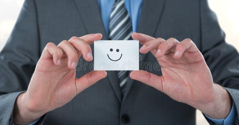 Midsection av den hållande smileyframsidan för affärsman på kort stock illustrationer