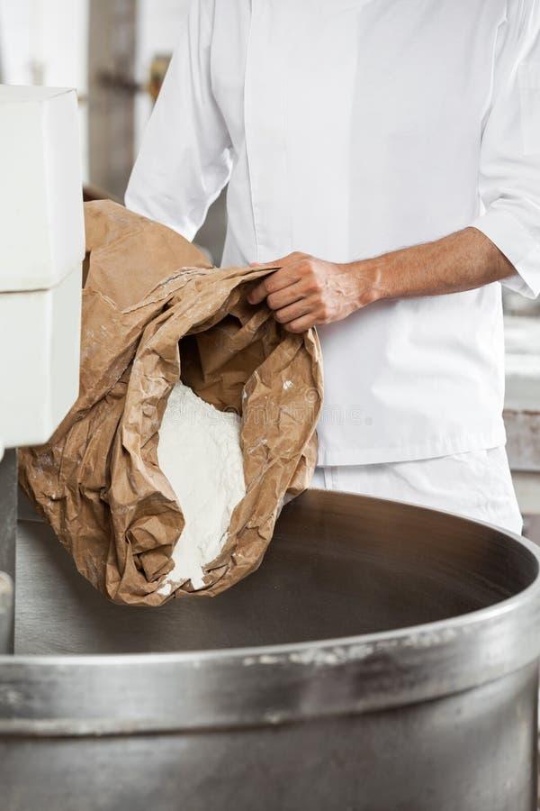 Midsection av den mogna bagaren Pouring Flour In som knådar maskinen arkivbild