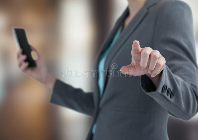 Midsection av den smarta telefonen för affärskvinnainnehav medan rörande imaginär skärm royaltyfri bild