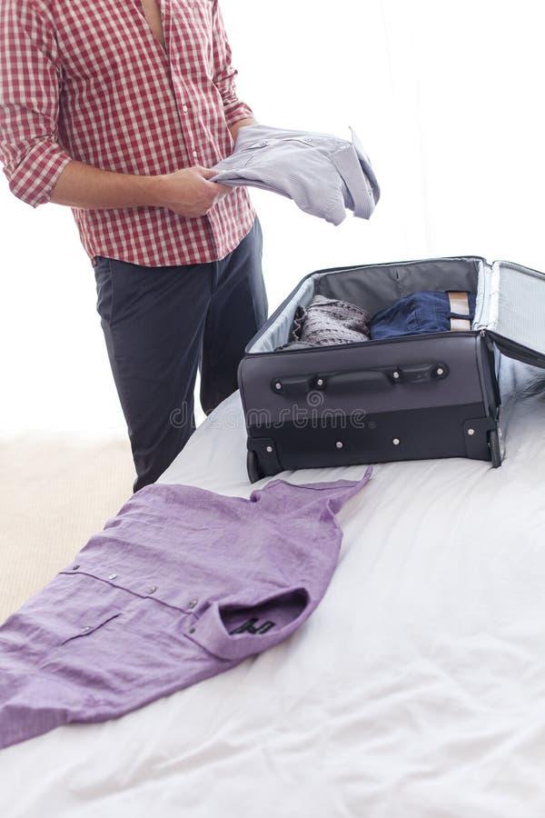 Midsection av den unga affärsmannen som packar upp bagage i hotellrum arkivbilder