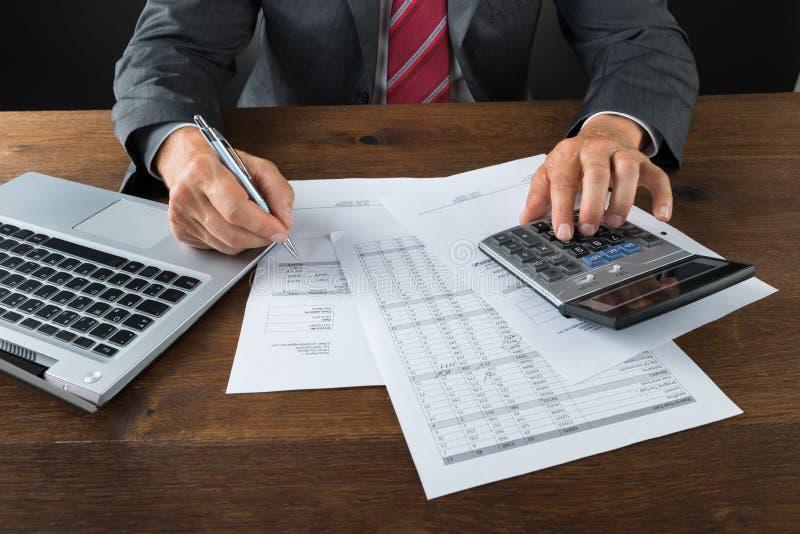 Midsection av det affärsmanChecking Bills At skrivbordet arkivbild