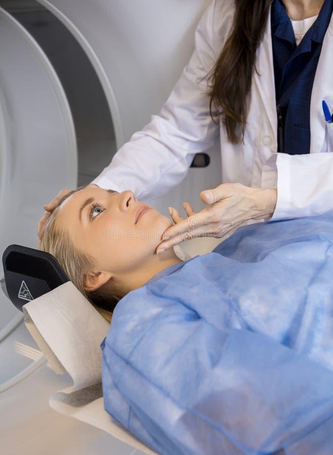 Midsection av doktorn Adjusting Patient & x27; s-framsida för MRI-bildläsning arkivbild