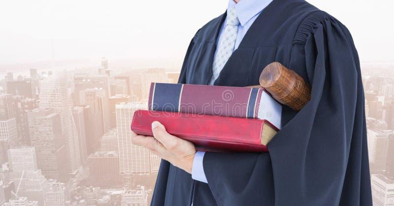Midsection av domaren med böcker och auktionsklubban mot stad royaltyfri foto