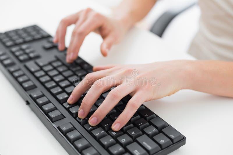 Midsection av en affärskvinnamaskinskrivning på tangentbordet arkivbilder