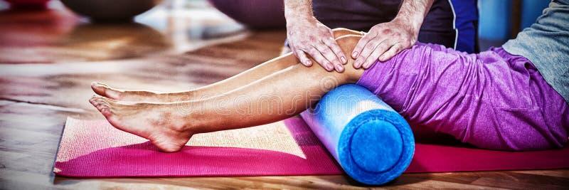 Midsection av fysioterapeuten som hjälper kvinnan, medan öva på den matta övningen arkivfoto