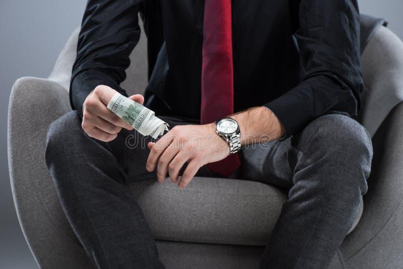 Midsection av hållande pengar för affärsman i händer, medan sitta på fåtöljen, royaltyfri illustrationer