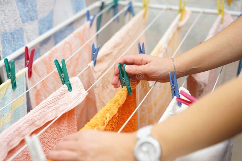 Midsection av kvinnahänder som hänger upp tvätteri arkivbild
