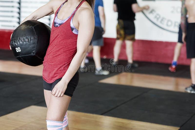 Midsection av kvinnan med den bärande medicinbollen för perfekt kropp arkivfoto