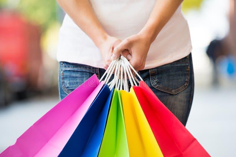 Midsection av kvinnan som rymmer färgrika shoppingpåsar royaltyfri bild