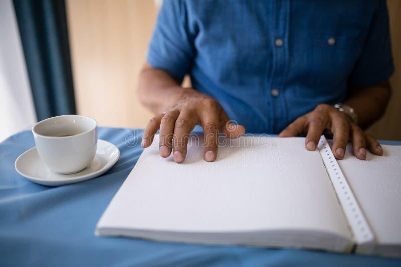 Midsection av läseboken för hög man vid kaffekoppen på tabellen royaltyfria foton