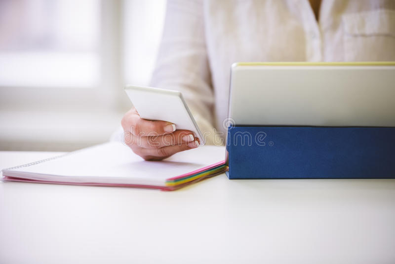 Midsection av ledaren med trådlösa teknologier på skrivbordet i regeringsställning royaltyfri foto