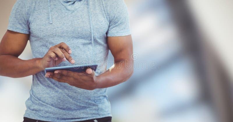 Midsection av mannen som använder den digitala minnestavlan mot suddig bakgrund arkivfoto