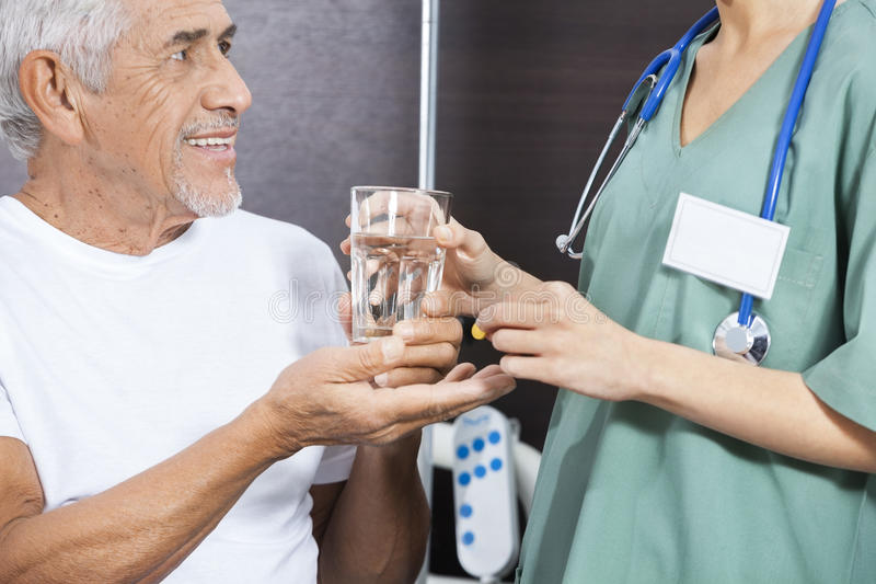 Midsection av sjuksköterskaGiving Medicine And vatten till den höga patienten arkivfoton