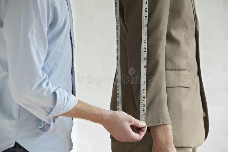 Midsection av skräddareMeasurings Customers dräkt arkivbilder