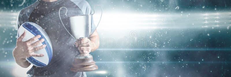 Midsection av trofén och bollen för lyckad rugbyspelare den hållande royaltyfri bild
