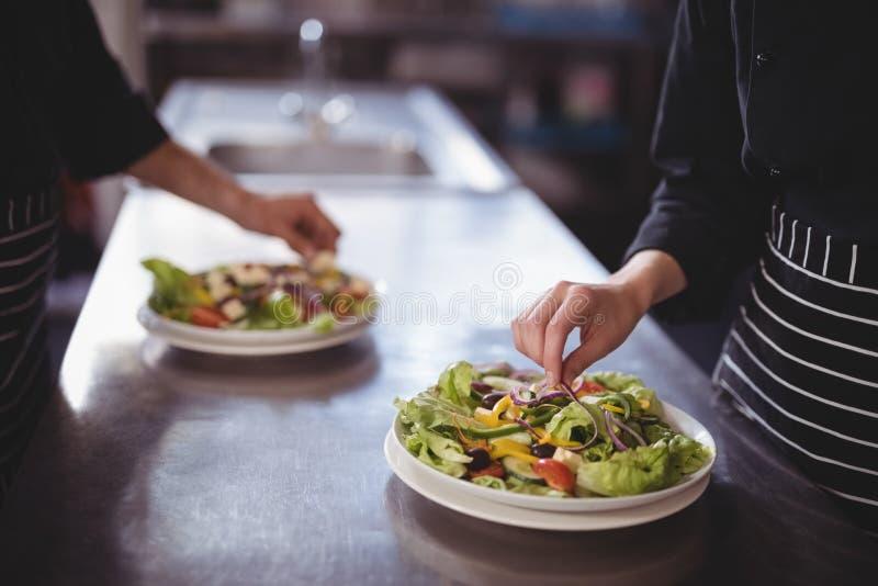 Midsection av uppassaren och servitrins som förbereder ny sallad i kommersiellt kök royaltyfri foto