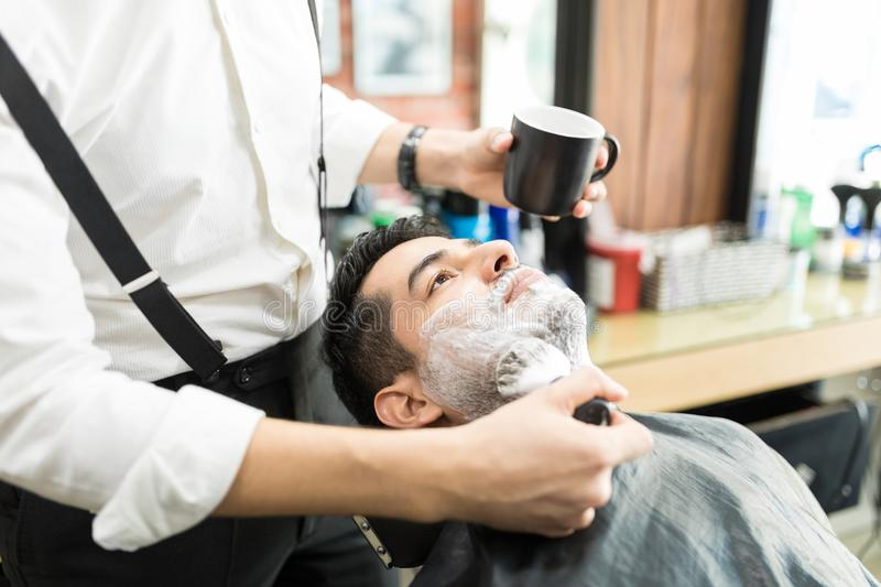 Barber Spreading Shaving Foam With Brush On Man`s Face stock images
