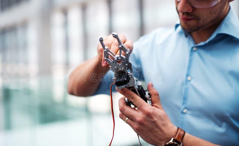 Midsection biznesmen lub naukowiec z mechaniczną ręki pozycją w biurze, pracuje zdjęcia stock