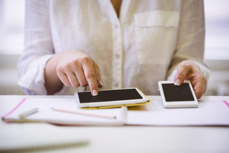 Midsection bizneswoman z technologiami bezprzewodowymi przy biurkiem w biurze fotografia stock