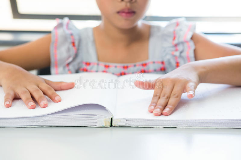 Midsection of blind girl reading braille book. In classroom royalty free stock image