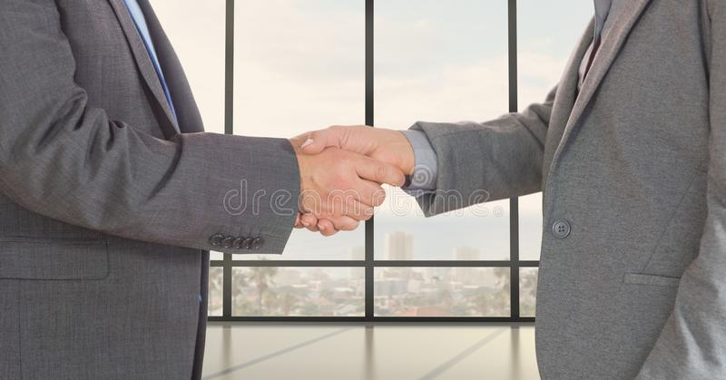 Midsection of business professionals shaking hands stock images