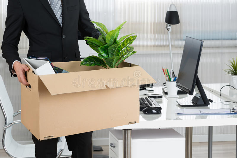 Midsection Of Businessman Carrying Cardboard Box royalty free stock photography