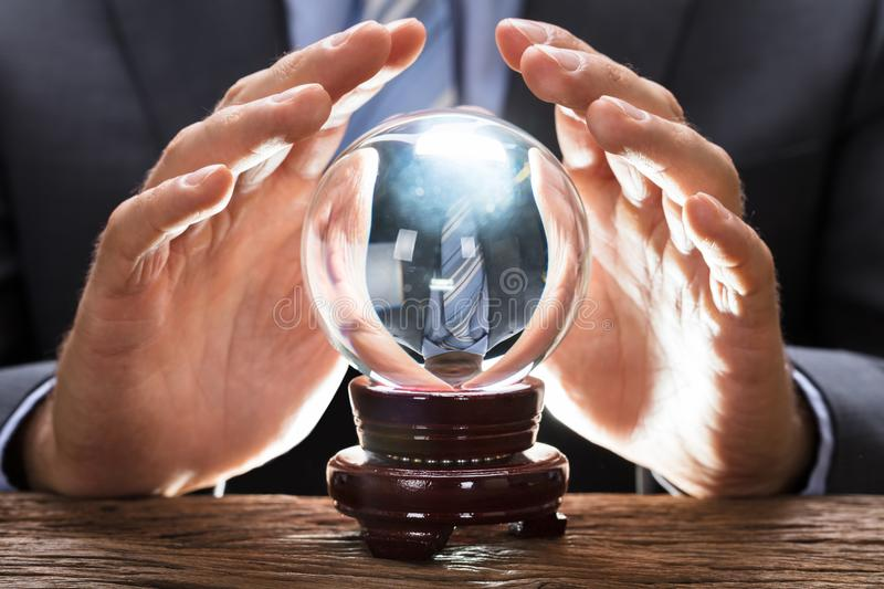 Midsection Of Businessman Covering Crystal Ball stock photo