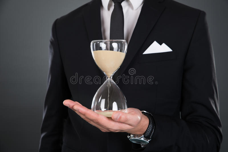 Midsection of businessman holding hourglass stock photos