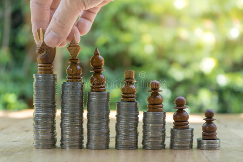 Midsection of businessman placing chess pieces on stacked coins royalty free stock photo