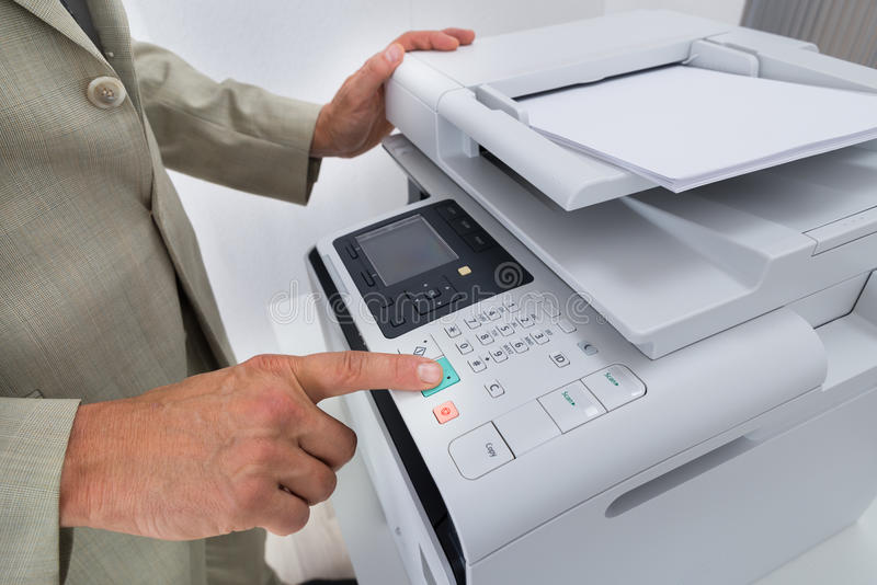 Midsection Of Businessman Pressing Printer's Button stock photo
